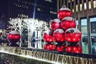 How to Save Money During the Holidays: 7 Top Tips   Sculpture of giant red Christmas ornaments in New York City   Photo by Daye Deura