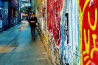 6 Essential Types of Insurance for Self-Employed Workers That People Often Forget   Photo of a man working on his phone as he walks down an alley with graffiti   Photo by Daye Deura