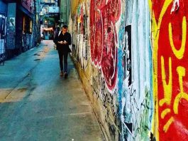 6 Essential Types of Insurance for Self-Employed Workers That People Often Forget | Photo of a man working on his phone as he walks down an alley with graffiti | Photo by Daye Deura