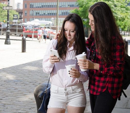 What is an IRA? How does an IRA Work? | Two women holding coffee and looking at a phone | Photo by Eric Strausman
