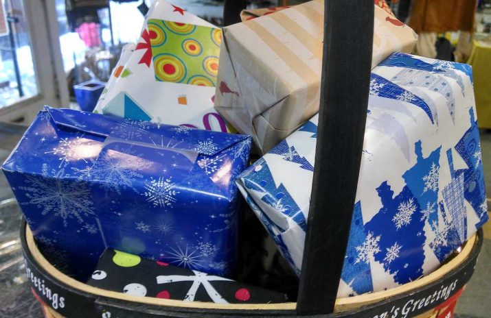 Cheap Gift Ideas: 6 Tips Buy Used Gifts and Not Get Caught | Photo of wrapped holiday gifts in a basket | Photo by Evan Sachs