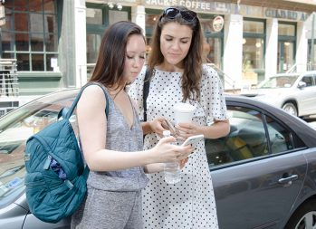 How to repair credit | Photo of two women looking at a cell phone | Photo by Eric Strausman