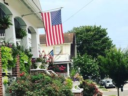 When and How to Work From Home: Amazon work-from-home jobs | Photo of a suburban house with an American flag | Photo by Rita Pouppirt