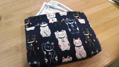 What is a money market account? How does a money market account work? | Photo of a wallet with a Japanese pattern of good luck cats; money sticking out of a wallet | Photo by Evan Sachs