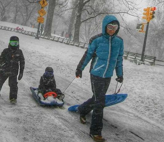The Best Things in Life Are Free: 10 Free Activities | Photo of a father and his children going sledding | Photo by Daye Deura