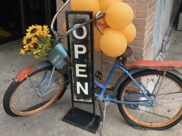"The Pros and Cons of Small-Business Credit Cards | Photo of an ""open"" sign with an antique blue bike propped up against it 