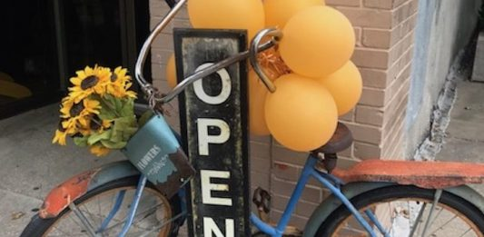 """The Pros and Cons of Small-Business Credit Cards   Photo of an """"open"""" sign with an antique blue bike propped up against it   Photo by Rita Pouppirt"""