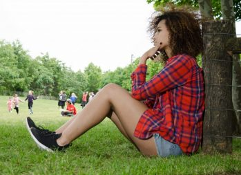 Women and Debt: A Feminist Issue? | Photo of a young woman sitting on a lawn and thinking | Photo by Eric Strausman