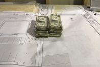 What is a certificate of deposit? How do CDs work? | Photo of money sitting on a blueprint | Photo by Rita Pouppirt
