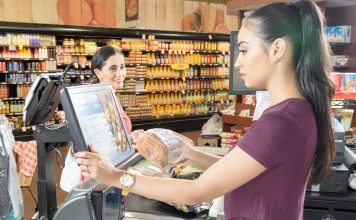 The Gainful Employment Rule and Student Debt: A Breakdown | Photo of a young woman working as a cashier at a supermarket | Photo by Eric Strausman