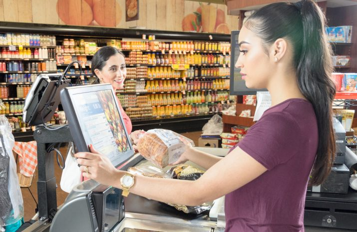The Gainful Employment Rule and Student Debt: A Breakdown   Photo of a young woman working as a cashier at a supermarket   Photo by Eric Strausman