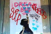 "How to Stick to New Year's Resolutions and Meet Financial Goals | Graffiti of a girl painting the words ""Dream Big"" 