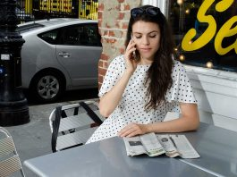 Chapter 7 vs. Chapter 13 Bankruptcy: What's the Difference?   Woman sitting at an outdoor table and talking on the phone while reading a newspaper   Photo by Eric Strausman