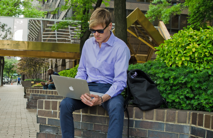 5 Employee Perks That You're Sure to Love | Photo of man in a dress shirt working on his laptop outside | Photo by Eric Strausman