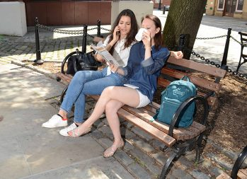 Why Is Financial Literacy Important? A Guide for Millennials | Photo of two women sitting on a bench with a newspaper and coffee | Photo by Eric Strausman