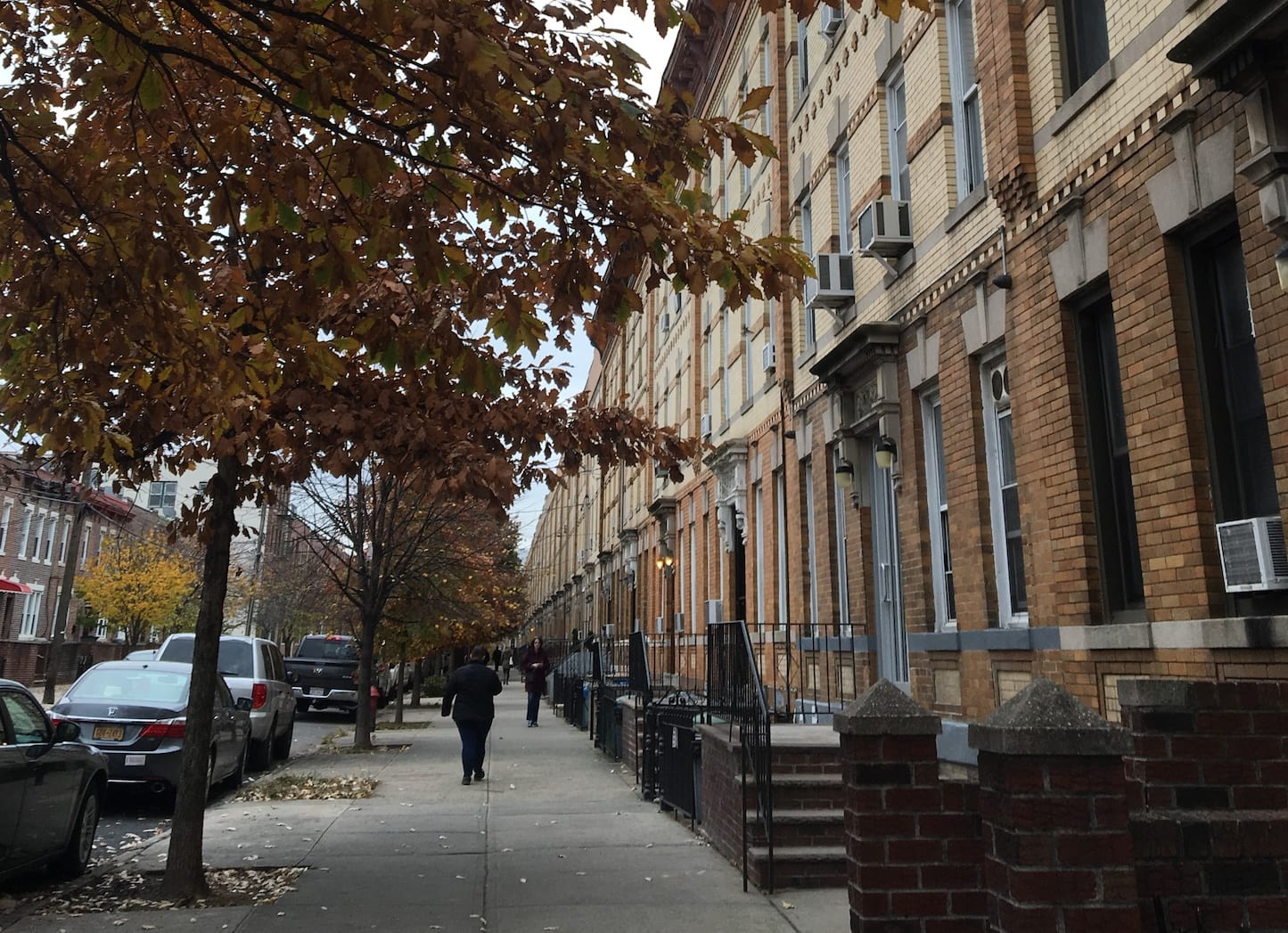 Effects of Poverty: Can You Be Too Poor for Financial Literacy? | Photo of somebody walking down the sidewalk past rows of apartments | Photo by Emma Finnerty